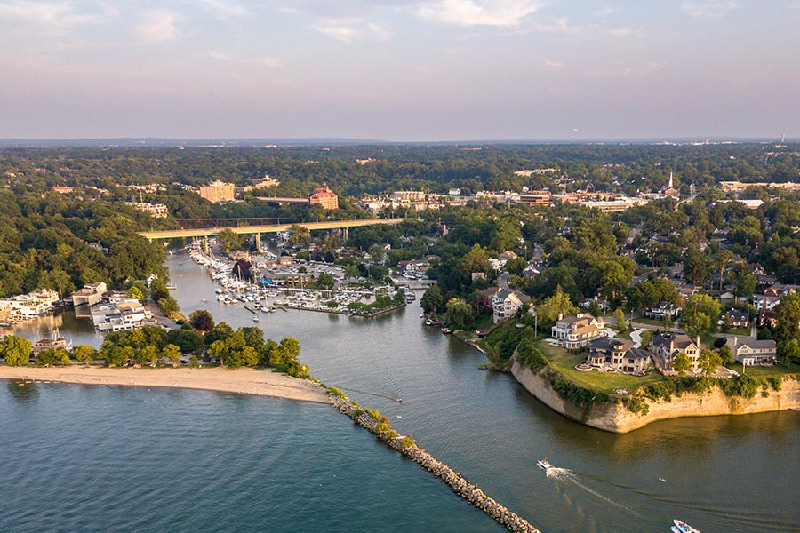 About Our Agency - Aerial View Of Rocky River, Ohio Shoreline on a Partly Cloudy Day, The Jetty and Water In the Foreground