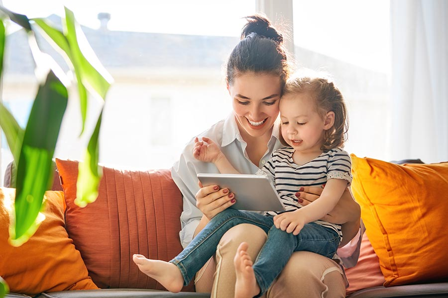 Blog - Mom and Young Daughter Use a Tablet on Their Bright Orange Sofa, a Houseplant in the Foreground